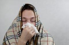 Den kalla mannen slogg sig in i en varm filt och blåser hans näsa i en näsduk begrepp: sjukdomar förkylningar Royaltyfri Foto