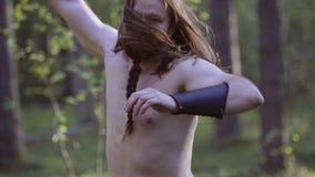 Den kalla mannen som är naken på torson med en kniv i hans hand, utför en knivattack i riktningen av kameran Utbildande melee med arkivfilmer