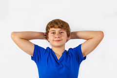 Den kalla pojken håller hans armar bak hans huvud Arkivfoto