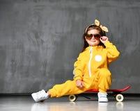 Den kalla ungeflickan i gul med huva jumpsuitdräkt, solglasögon och gul pilbåge sitter i kallt poserar på den röda skateboarden fotografering för bildbyråer