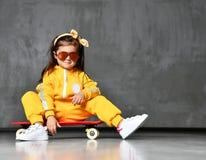 Den kalla ungeflickan i gul med huva jumpsuitdräkt, solglasögon och gul pilbåge sitter på skateboarden i kallt poserar som precis arkivfoton