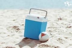 Den kallare asken och volleyboll klumpa ihop sig på den sandiga stranden arkivfoton