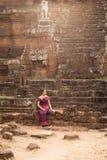 Den kambodjanska flickan i en khmerklänning sitter på Phimeanakas i Angkor Thom Fotografering för Bildbyråer