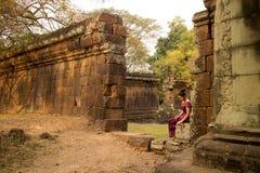 Den kambodjanska flickan i en khmerklänning sitter vid en stenvägg i Angkor Thom Arkivfoton