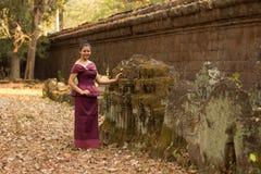 Den kambodjanska flickan i en khmerklänning står vid sned stenar i Angkor Thom Arkivbild