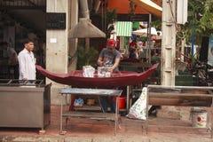 Den kambodjanska mannen klipper is på en gata Royaltyfri Foto
