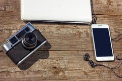 Den kameratelefonen och bärbara datorn är på en trätabell royaltyfria foton