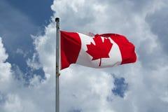 Den kanadensiska flaggan flyger proudly mot en blå molnig himmel Arkivfoto
