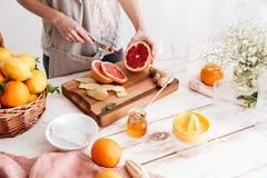 Den kantjusterade bilden av den unga kvinnan klippte grapefrukten Arkivbild