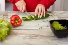 Den kantjusterade bilden av kvinnans grönsaker för handsnitt med kniven, skivor gurka, peppar och grönsallat på köksbordet, förbe arkivbild