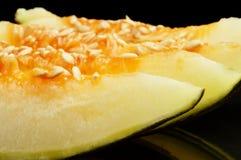 Den kantjusterade gröna melon för fotoPiel de sapo stycken isolerade svart Royaltyfri Fotografi