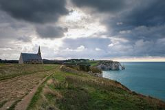 Den kapellNotre-Dame de laen Garde och kalkstenklipporna av Etretat med en sikt av havet i Oktober, Frankrike royaltyfri fotografi