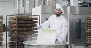Den karismatiska bagarekocken lastade av mjölet i en behållare i en stor bageribransch som han ler och har ett stort lynne arkivfilmer