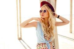 Den karismatiska blonda flickan med rund solglasögon och hatten tycker om solen på havet Horisontalsikt på den ljusa bakgrunden royaltyfria foton