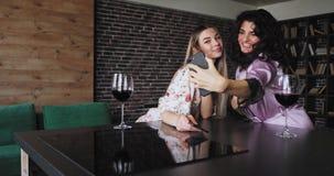 Den karismatiska damen för lockigt hår med hennes nätta vän i pyjamas tar selfiesna med smartphonen gör roliga framsidor in stock video