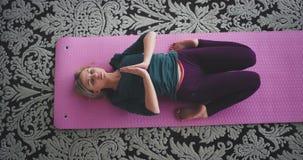 Den karismatiska damen har en meditation i morgonen som hon gör en yoga poserar för att få mer energi för hela dagen hemma på stock video