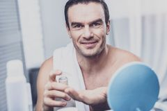 Den karismatiska modellen som applicerar raka skum till hans, gömma i handflatan royaltyfri foto