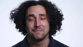 Den karismatiska skäggiga unga mannen i svart skjorta på vit bakgrund visar olika sinnesrörelser stock video