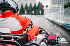 Den Karting racerbilen, går kartchauffören i hjälmen, baksidasikt arkivfoton
