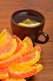 Den keramiska bruntet kuper med tea, och candied frukt på brunt stiger ombord Arkivfoto