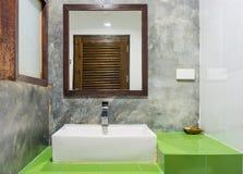 Den keramiska handfatet, bunken och spegeln på gröna keramiska tegelplattor kontrar Arkivbilder