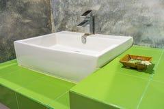 Den keramiska handfatet och bunken på gröna keramiska tegelplattor kontrar Arkivbild