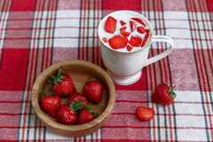 Den keramiska koppen av yoghurt, röda nya jordgubbar är i träplattan på kontrollbordduken Organisk sund smaklig mat för frukost Royaltyfria Bilder