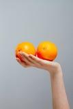 Den kinesiska apelsinen på den asiatiska kvinnahanden på grå färger hårdnar bakgrund royaltyfria foton