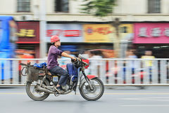 Den kinesiska arbetaren gasar på motorcykeln Royaltyfri Bild
