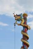 Den kinesiska drakestatyn rullar över polen Arkivfoto