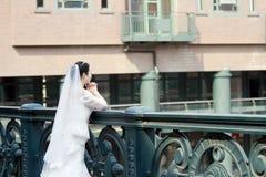 Den kinesiska flickabruden i bröllopsklänning med en härlig imperialistisk krona ber Royaltyfri Foto