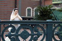 Den kinesiska flickabruden i bröllopsklänning med en härlig imperialistisk krona ber arkivbilder