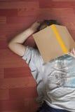 Den kinesiska flickan är trött att se notbooken och att falla sovande på golvet Arkivbild