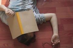 Den kinesiska flickan är trött att se notbooken och att falla sovande på golvet Arkivfoton