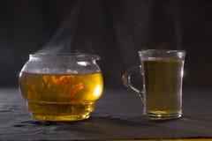 Den kinesiska knoppen för grönt te blommar i en glass tekanna En kupa av tea Arkivbild