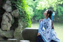 Den kinesiska kvinnan i den traditionella blått- och vitHanfu klänningen sitter på stenbänken Fotografering för Bildbyråer