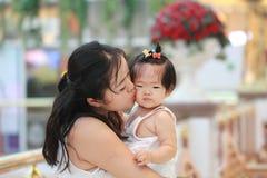 Den kinesiska kvinnan kysser hennes sött behandla som ett barn flickan på en galleria Fotografering för Bildbyråer