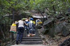 Den kinesiska manarbetaren, bär allt material till berget Huangshan royaltyfria foton