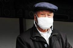Den kinesiska manen ha på sig kirurgiskt maskerar Arkivfoto
