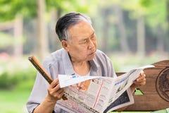 Den kinesiska manliga pensionären läser en tidning i en parkera, Peking, Kina Arkivbilder