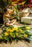Den kinesiska mannen säljer buketter av nya blommor på gatan av Bugis, Singapore royaltyfri fotografi