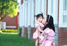 Den kinesiska modern kysser hennes lilla dotter royaltyfri foto