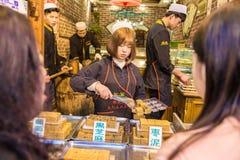 Den kinesiska muselmanen shoppar mat för personalpackemellanmålet för hennes kunder på Arkivbild
