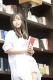 Den kinesiska ståenden av ung härlig kvinnahållutbildning bokar i bokhandel Royaltyfri Fotografi
