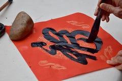 Den kinesiska teckenöversättningen för kalligrafi A är lycka Arkivfoton
