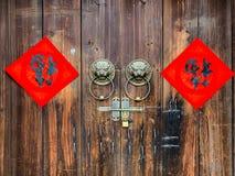 Den kinesiska välsignelsen Fu för handskrift på trädörren med traditionell kines brons handtaget arkivfoto