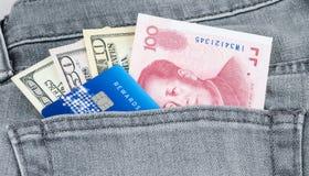 Den kinesiska yuanen, US dollarsedeln och kreditkorten i den gråa jeanen stoppa i fickan Royaltyfri Foto