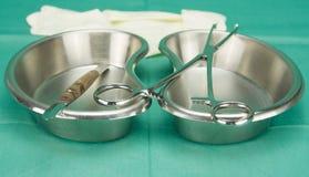 Den kirurgiska klämman och kniven som förläggas på njureform, bowlar Royaltyfria Bilder