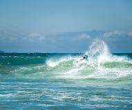 Den Kitesurfer idrottsmannen gör akrobatiskt trick på stor havsvåg Royaltyfri Bild