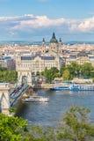 Den klara sikten för vårdagen av den Chain bron, Donauen och basilika för helgonIstvan ` s från Buda rockerar område i Budapest,  Royaltyfri Fotografi